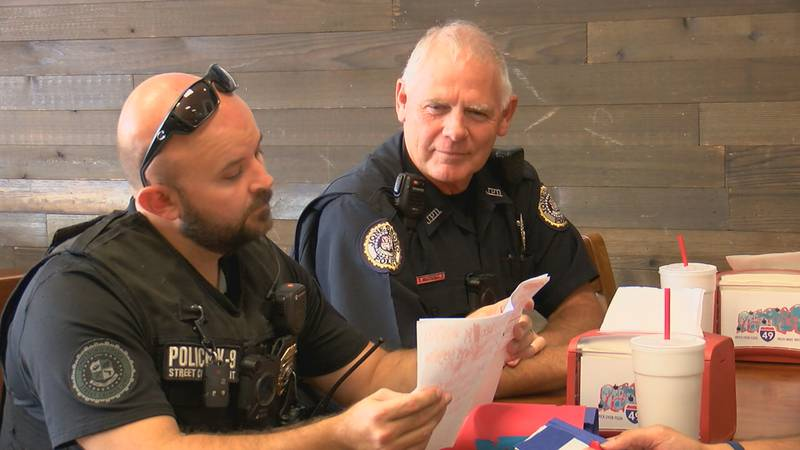 Jonesboro police officers wait for their free pizza at Pastaria 49.