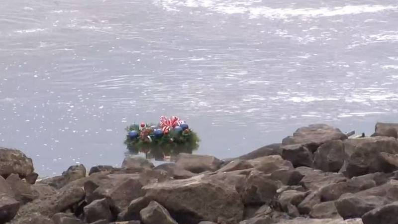 A wreath along with roses and other flowers were dropped into the Mississippi River in honor of...