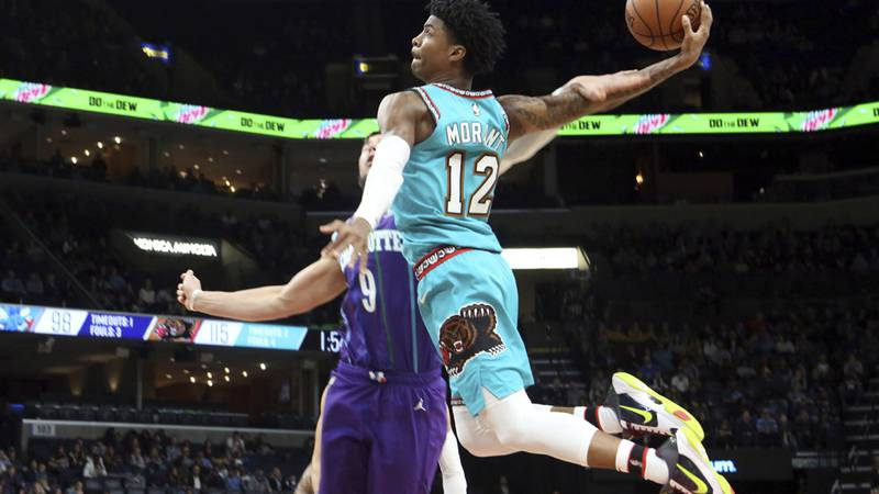 Memphis Grizzlies guard Ja Morant (12) goes up to shoots while defended by Charlotte Hornets...