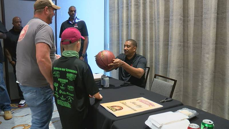 Scotty Thurman signs a basketball for two fans at the Hogs Hoops Reunion Saturday.