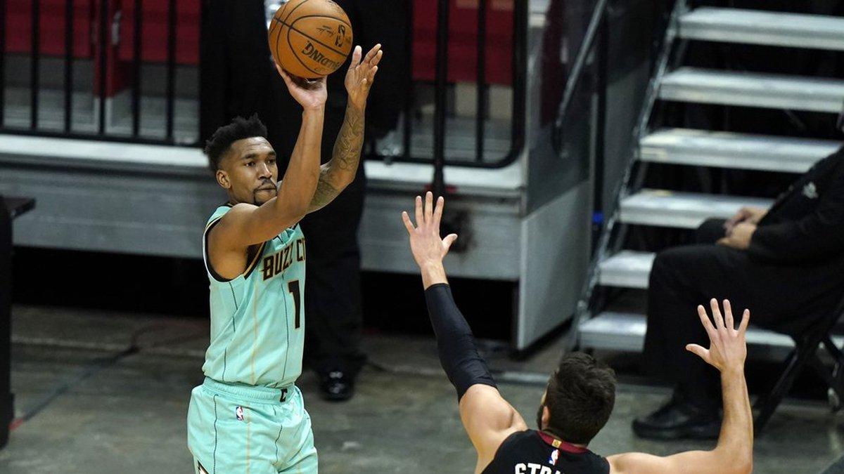 Charlotte Hornets guard Malik Monk (1) shoots a 3-pointer as Miami Heat guard Max Strus (31)...