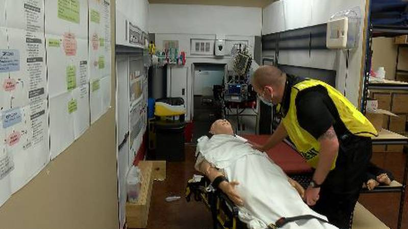 A EMT student wheels a man into a working area for a vital check.