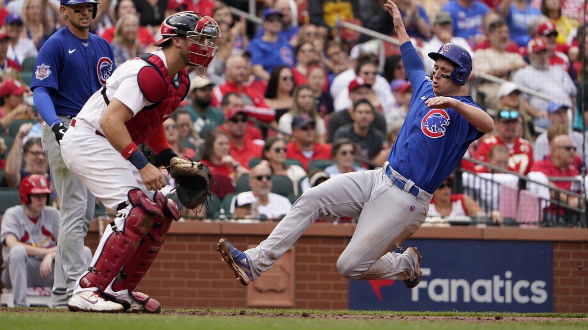 Chicago Cubs' Frank Schwindel, right, scores past St. Louis Cardinals catcher Andrew Knizner...
