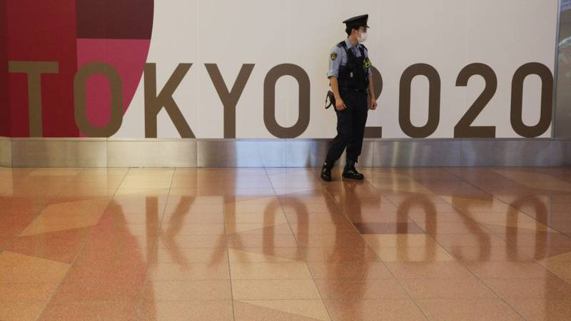 A police officer stands in front of Tokyo 2020 Olympic display at Haneda international airport...