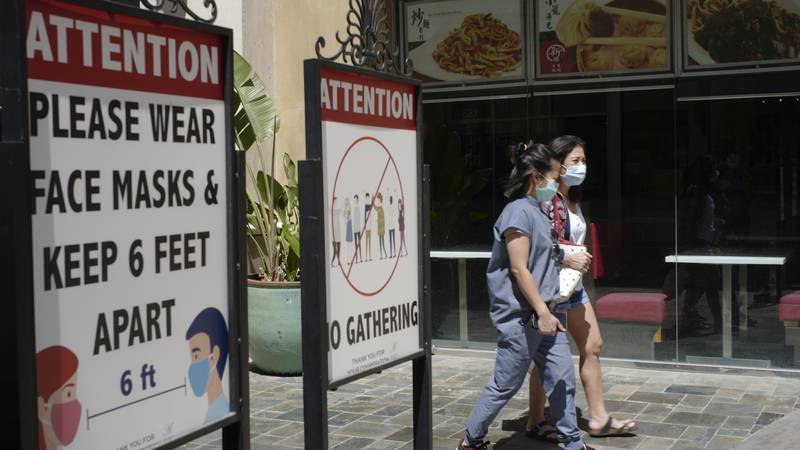 File - In this June 11, 2021 file photo customers wear face masks in an outdoor mall with...