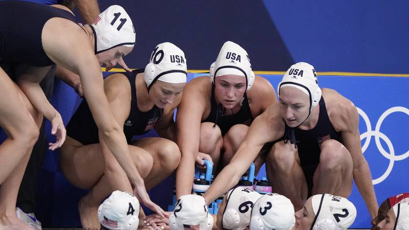 United States players huddle during a timeout in a preliminary round women's water polo match...