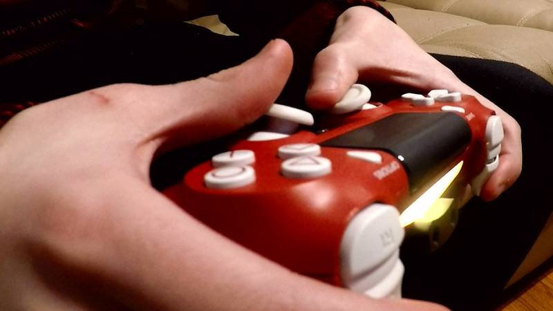 Boy holding video game controller playing online video games