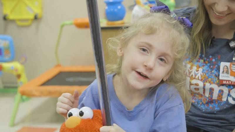 Kimber swinging in her classroom. She once lacked the muscle tone to keep her balance.
