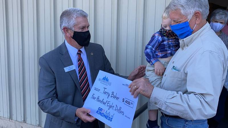 First Community Bank's David Daniel presenting Terry Baker with a commemorative check for...